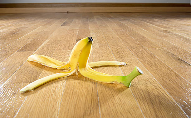 Banana Peel on Parquet Floor Risk concept: Banana peel on parquet floor.  banana peel stock pictures, royalty-free photos & images