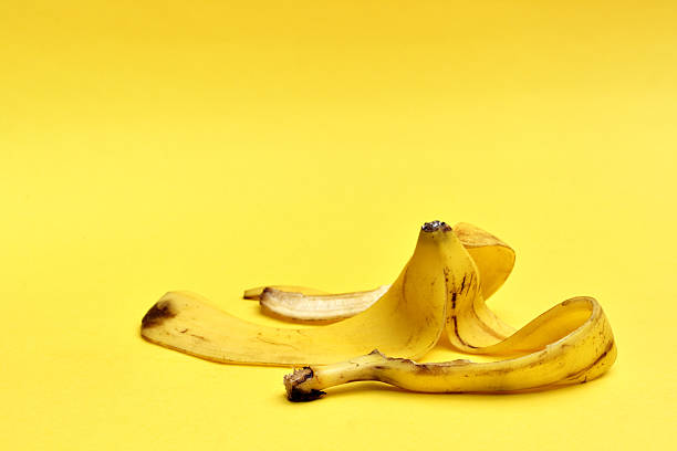 banana peel on yellow background stock photo