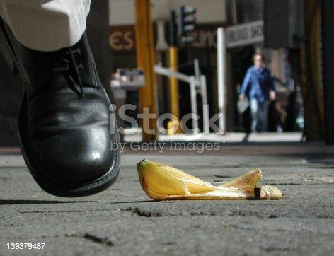 Man nearly steps on a banana peel on a city street.