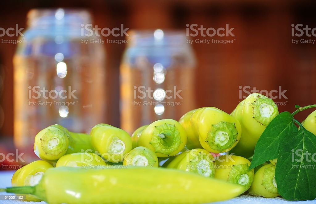 Banana peppers and glass jars in the background. stock photo