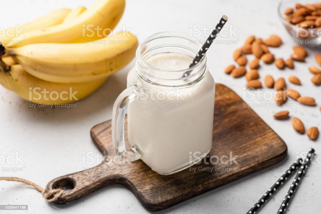 Banana protein smoothie in drinking glass stock photo