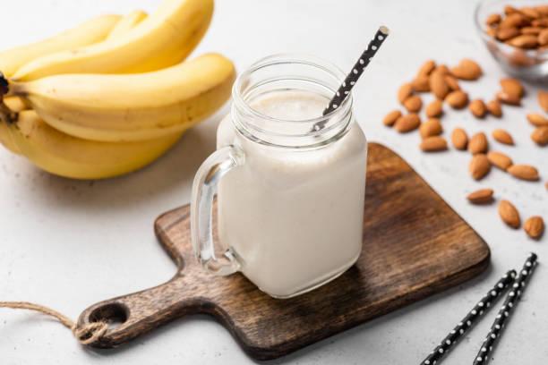 banaan eiwit smoothie in een glas drinken - yoghurtdrankje stockfoto's en -beelden