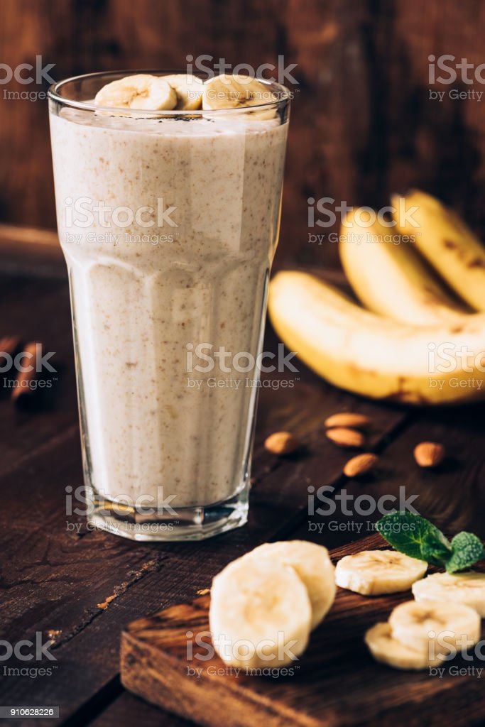 Banana smoothie in glass on brown wooden table stock photo
