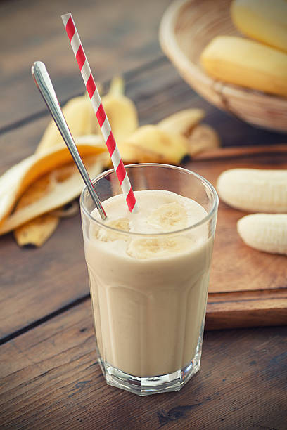 Banana smoothie in glass tumbler with straw and spoon in it stock photo