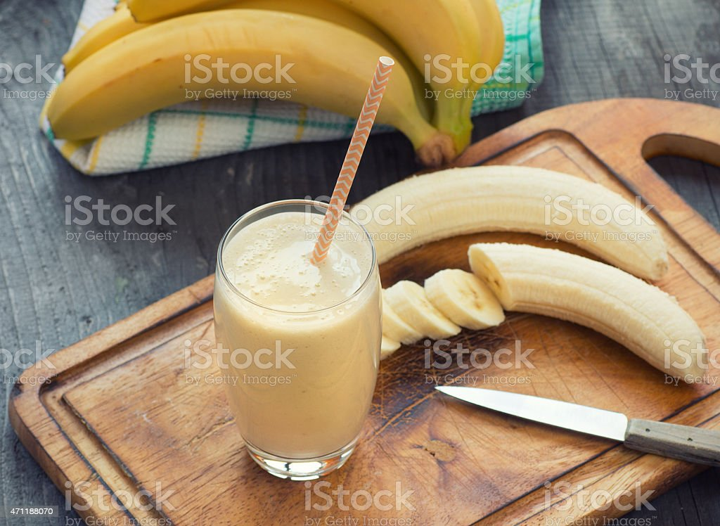 Banana smoothie on wooden board with fresh bananas stock photo