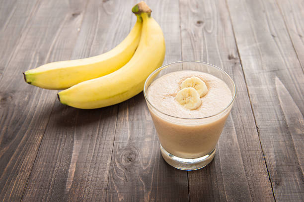 banana smoothie on wooden table. stock photo