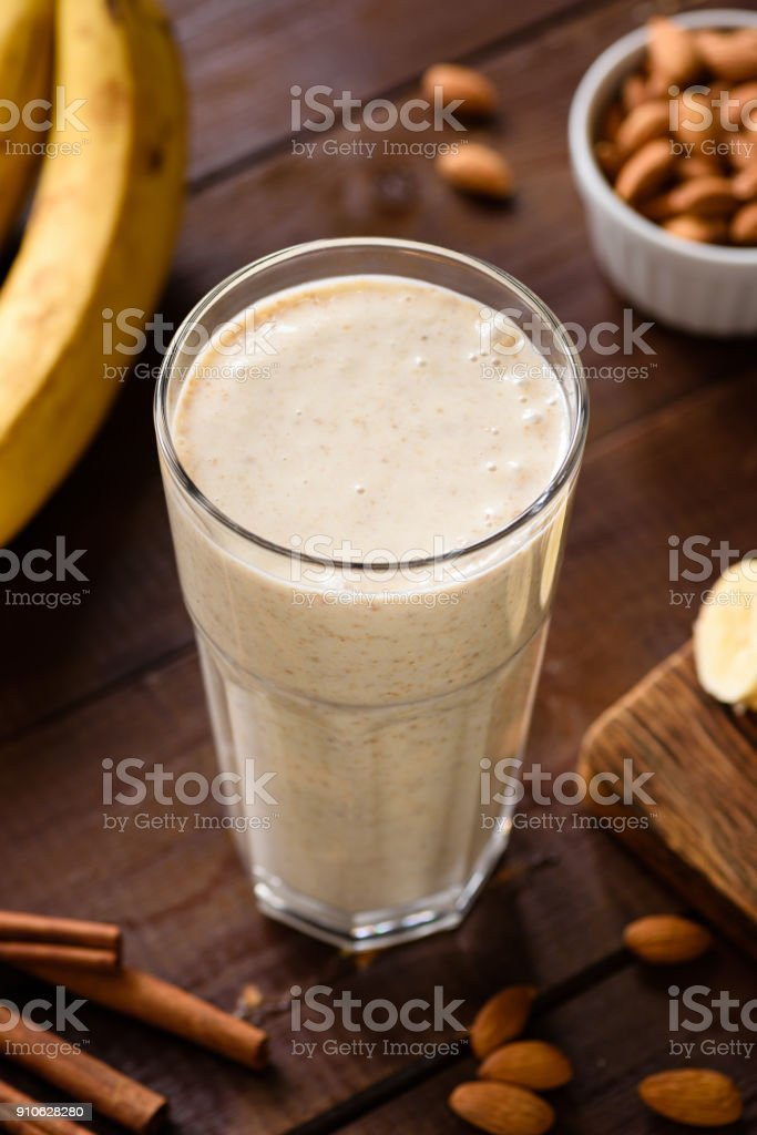 Banana smoothie with almond milk and cinnamon in glass on wooden table stock photo
