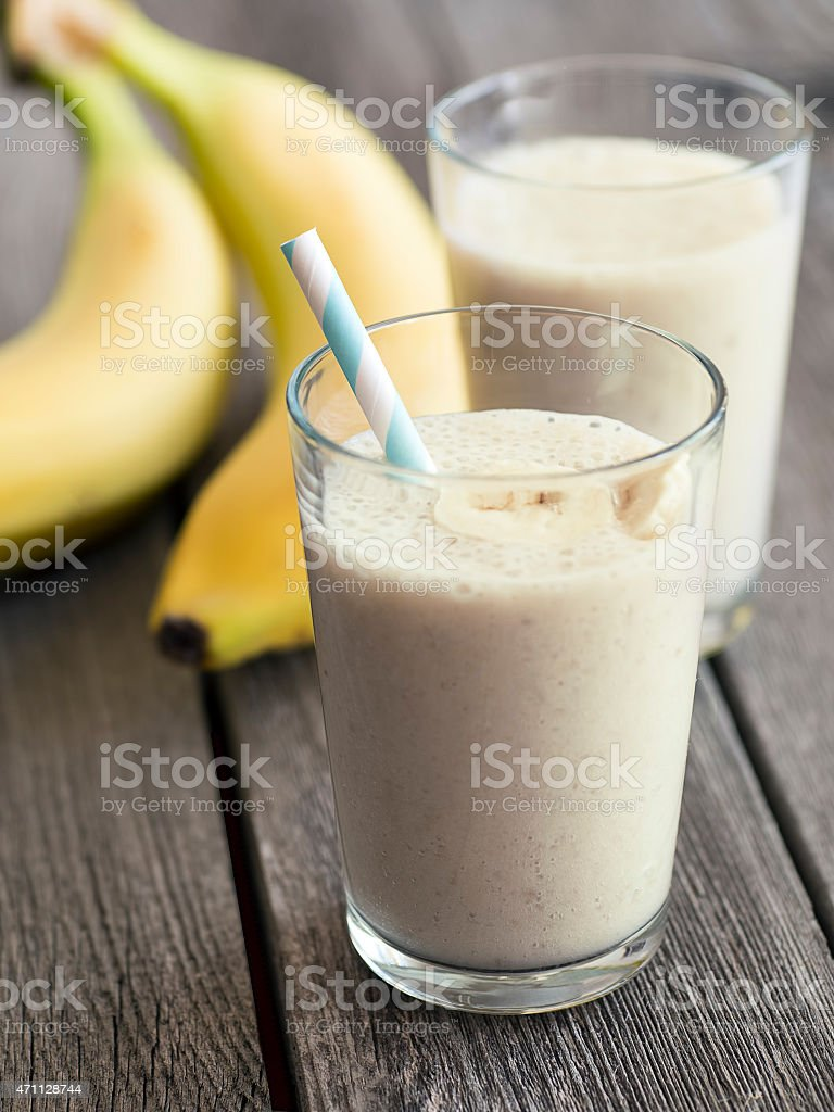 Banana smoothie with banan slices and drinking straw stock photo
