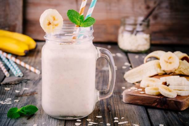 bananen-smoothie mit haferflocken in einmachglas auf einem hölzernen hintergrund - rustikale einweckgläser stock-fotos und bilder