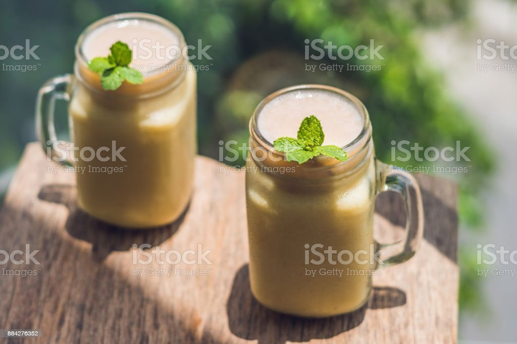 Banana smoothies and bananas on an old wooden background stock photo
