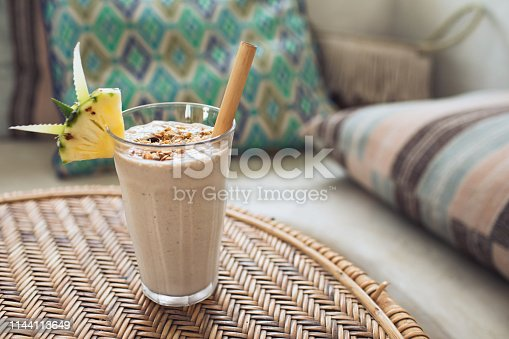 Glass with tasty banana smoothie with walnut paste with granola and pineapple on top. Vegetarian healthy breakfast protein smoothie on rattan table. Organic and well being concept.