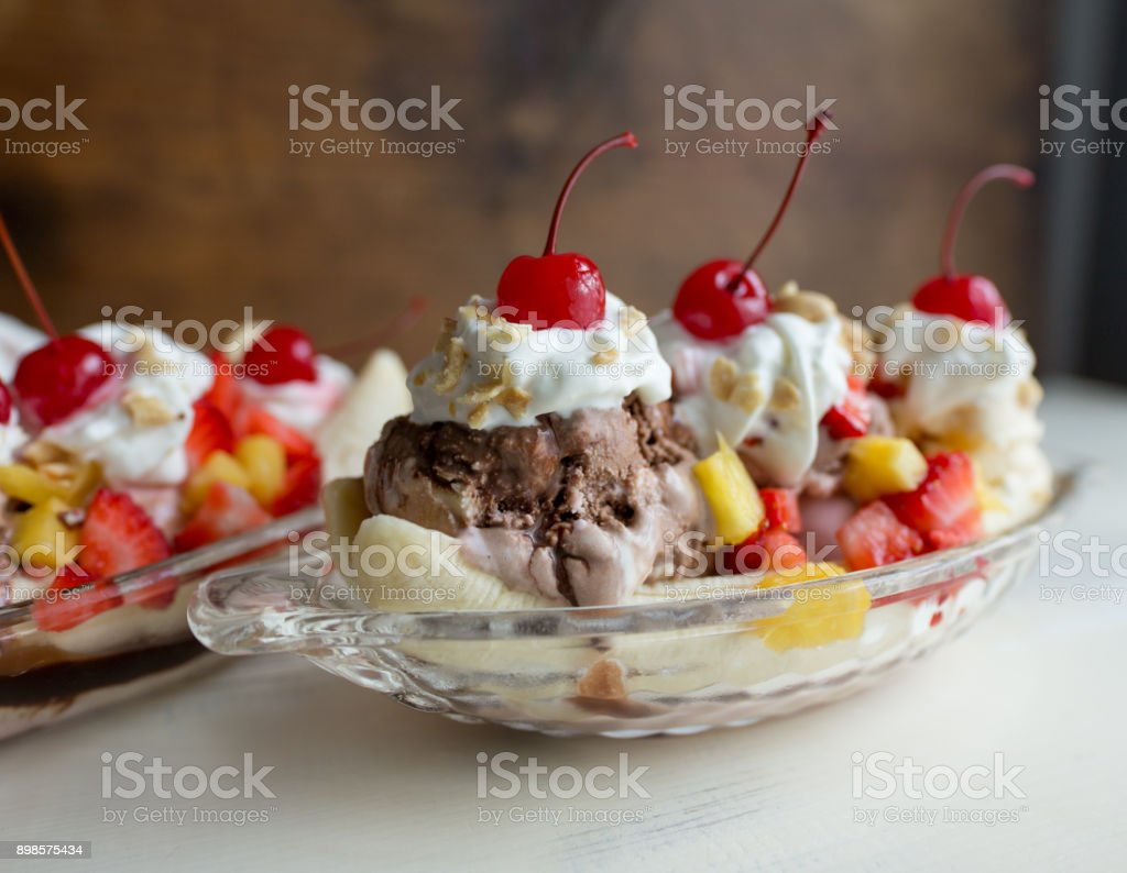 Banana splits in clear glass boats with strawberries, pineapple and cherry garnish. stock photo