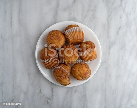 Top view of several banana Streusel muffins on a white plate atop a marble tabletop.