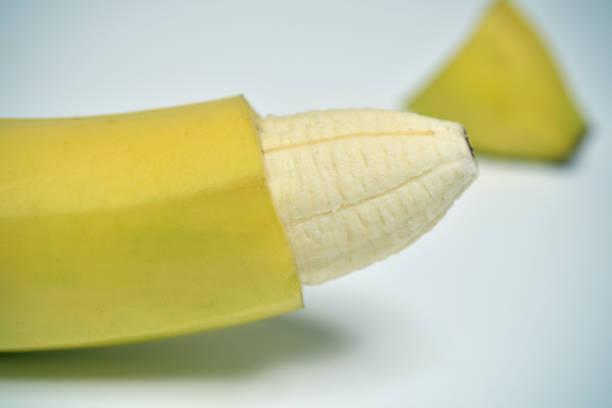 banane avec la peau de sa pointe enlevée - circoncision photos et images de collection