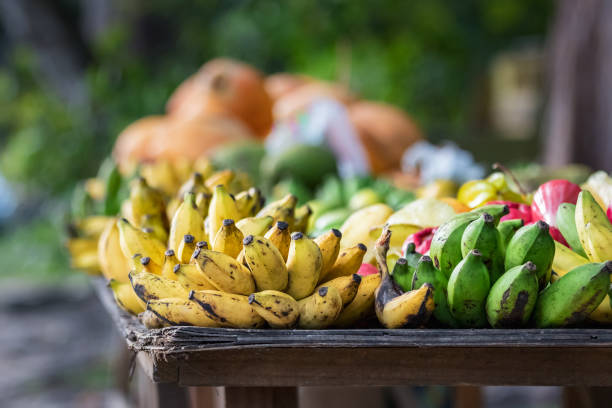 Bananas and green platanos oon a wooden table outdoors on the main street of Praslin, Seychelles stock photo