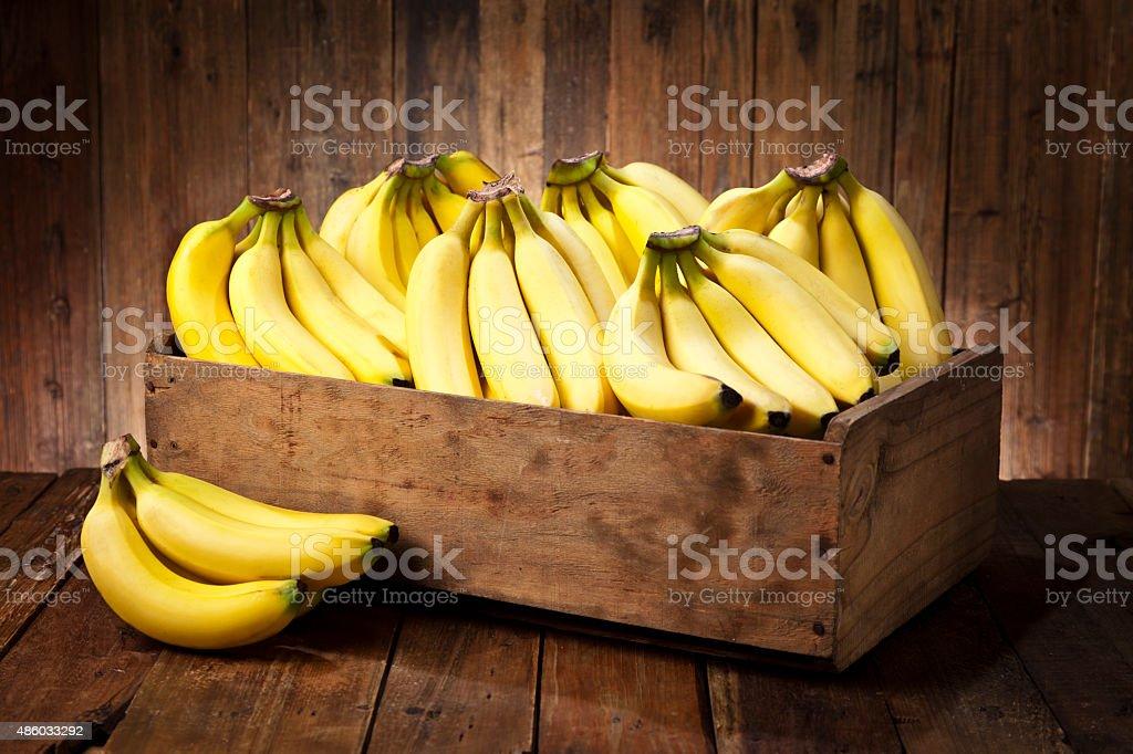 Bananas in a crate on rustic wood table bildbanksfoto