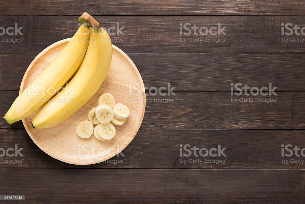 Bananas in a wooden dish on a wooden background. stock photo