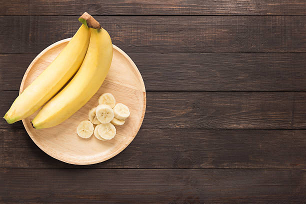 Bananas in a wooden dish on a wooden background. bildbanksfoto