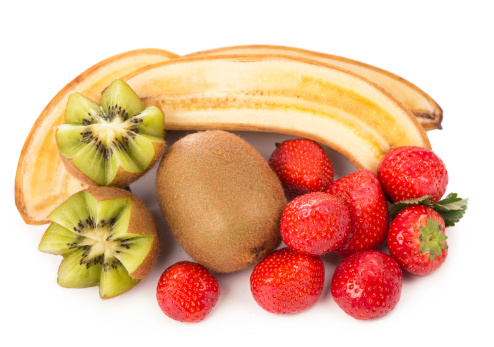 composition of yellow Bananas with green kiwi and red strawberries on a dark textured background.