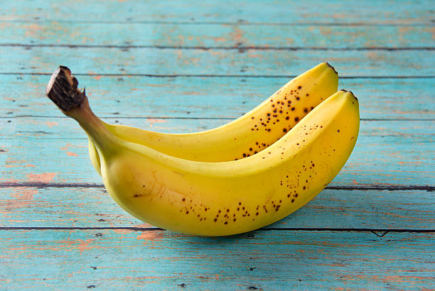 bananas on a wooden table - ripe stock photos and pictures