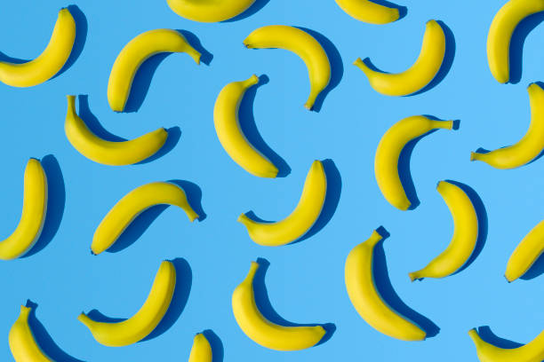 bananas on blue background - vibrant color stock pictures, royalty-free photos & images
