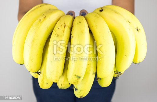 Woman hand holding a bunch  of fresh bananas. High resolution image.