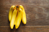 Bunches of fresh yellow bananas on wooden shelves in shop