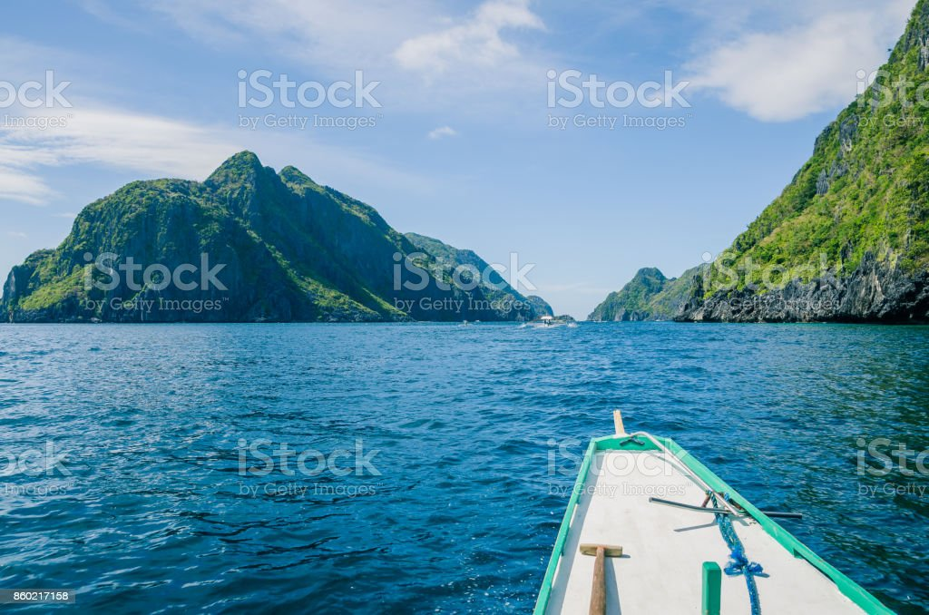 Banca Boat approaching Mantiloc Island on Windy Day, El, Nido, Palawan Philippines stock photo