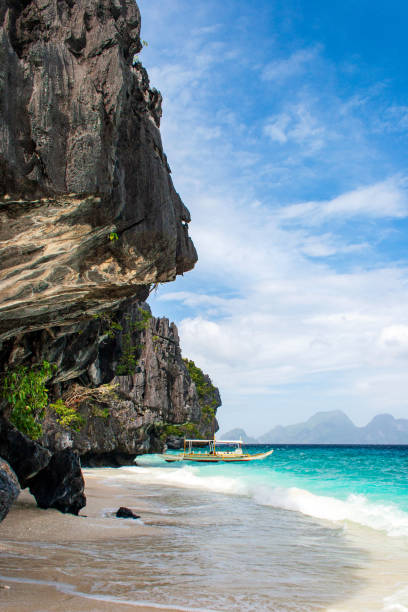 Banca boat on the pristine beach of Entalula island in El nido, region of Palawan in the Philippines. Vertical view. stock photo