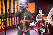 Portrait of modern hip-hop singer performing with his band in recording studio while making new album, copy space