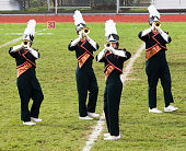 Trumpet line performing a halftime show. Focus on face visible in player facing left.