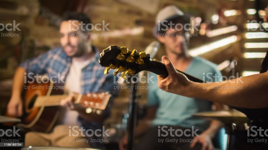 Band sing and play guitars while recording a song and practicing in a...