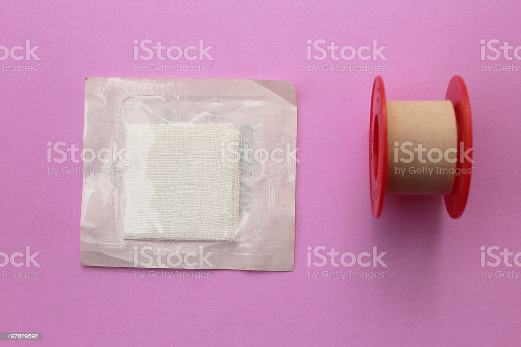Bandage and gauze - first aid concept on purple background stock photo