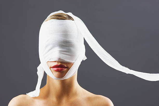 bandage covering woman's face - medical dressing stock pictures, royalty-free photos & images