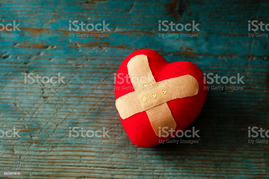 Band-aid covering a heart on a blue wooden background Band-aid covering a heart on a blue wooden background Adhesive Bandage Stock Photo