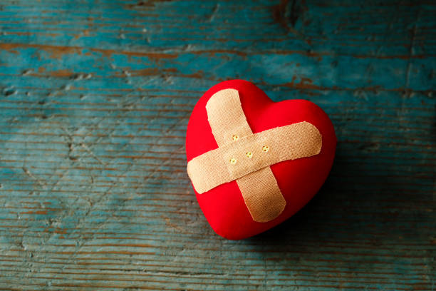 band-aid covering a heart on a blue wooden background - disappointment stock pictures, royalty-free photos & images