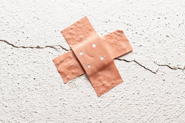band-aid pflaster in kreuz form auf einen riss in der wand, konzept für verpfuschten bau und raum kopieren um symptome, rakeln - pflasterbau stock-fotos und bilder