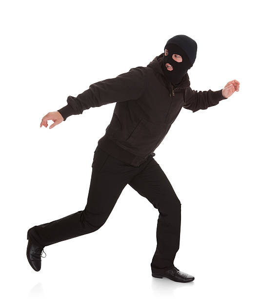 bandit in black mask running away - thief stock photos and pictures