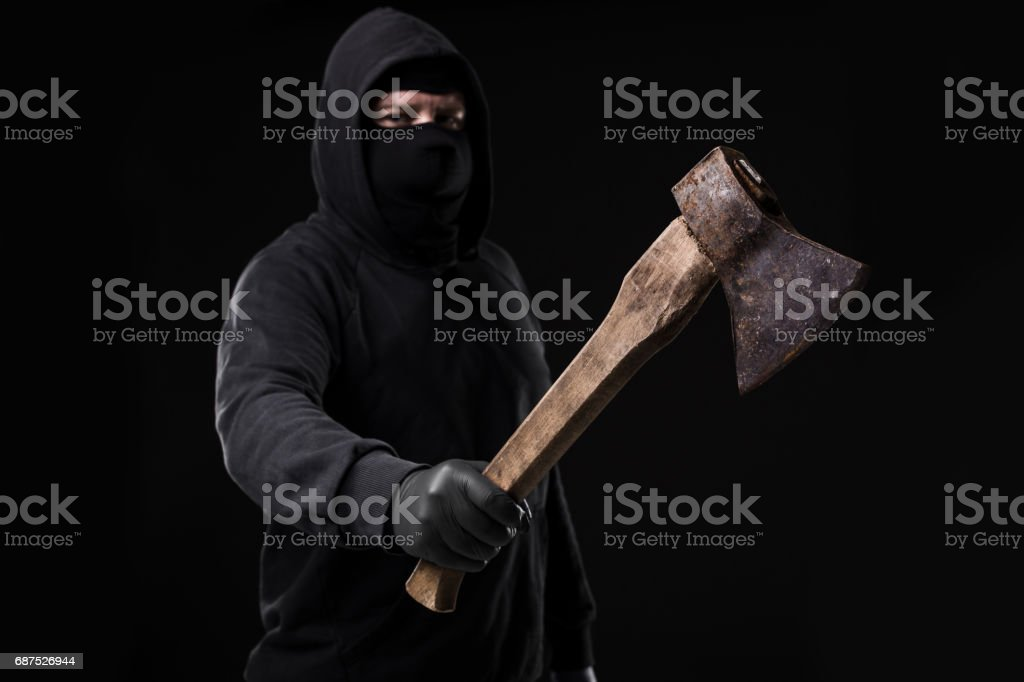Bandit in black mask with hatchet on black background stock photo