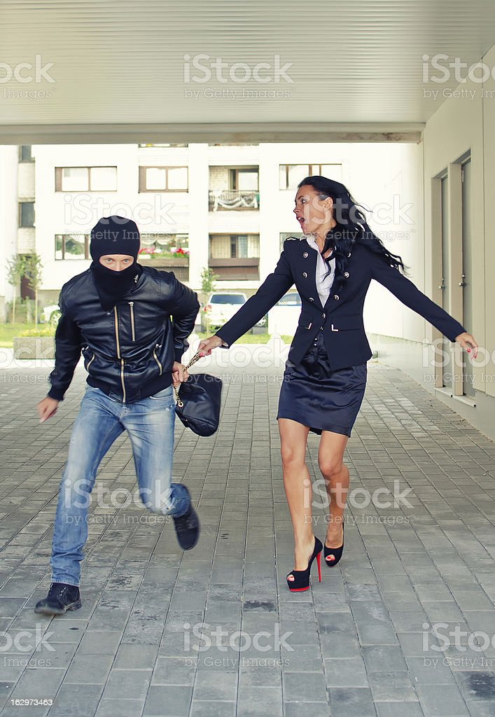 Bandit stealing businesswoman bag in the street royalty-free stock photo