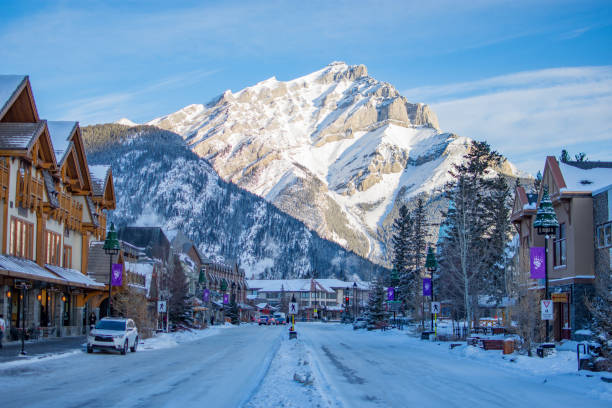 Banff Avenue in Snow Season, with this amazing view of Cascade Mountain. It takes your breath away every time. This view is seen many a time in famous movies and you can recreate it yourself. The view of Cascade Mountain in Banff, Canada, looking from Banff Avenue in winter, full of snow. banff national park stock pictures, royalty-free photos & images