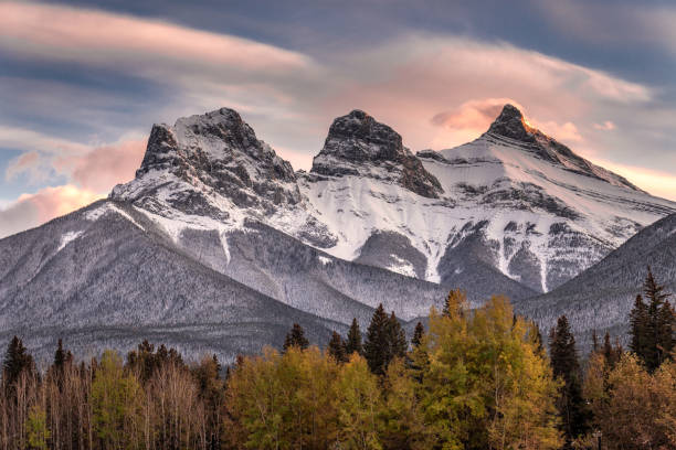 Banff National Park Sunset light just hitting the top of the Three Sister peaks near Canmore, Alberta, Canada alberta stock pictures, royalty-free photos & images