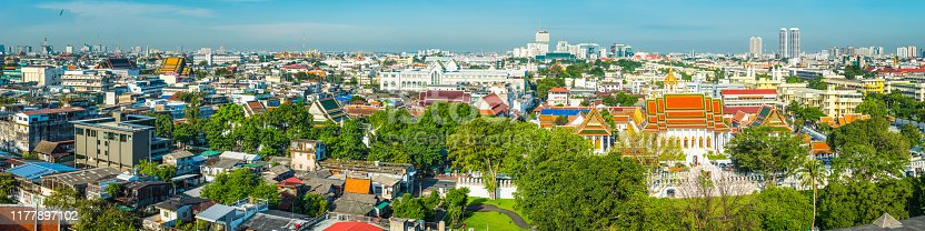 Aerial panoramic view over the terracotta rooftops of Wat Saket temple complex to the crowded cityscape of central Bangkok, Thailand's vibrant capital city.