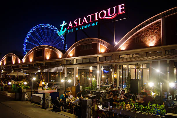 Bangkok - Asiatique The Riverfront Bangkok, Thailand - October 31, 2013: Diners having dinner around restaurants at Asiatique The Riverfront. The large-scale riverside development also features a mall, night market and a ferris wheel. thailand mall stock pictures, royalty-free photos & images