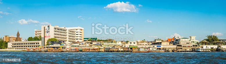 Panoramic view across the Chao Phraya to the traditional river ferries, bars and restaurants on the Bangkok waterfront in the heart of Thailand's vibrant capital city.