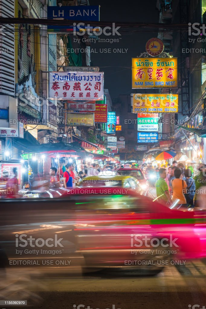 The neon signs of Yaorawat Road glowing at night above the crowds and...