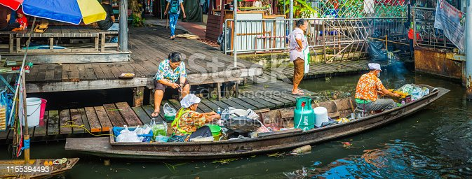 Local traders cooking food on a boat at a floating market in Bangkok, Thailand's vibrant capital city.