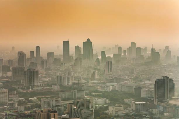 de skyline van bangkok in smog tijdens zonsondergang - smog stockfoto's en -beelden