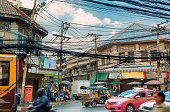 Lifestyle and street environment in Bangkok, Thailand. Traffic tuk tuk, pink taxis and traditional buses. Tangle of electric cables and house facades