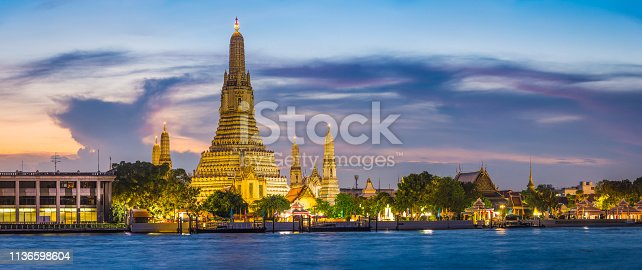 The iconic spire of Wat Arun spotlit against the blue dusk sky across the Chao Phraya River in the heart of Bangkok, Thailand's vibrant capital city.
